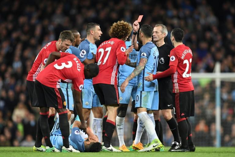 Referee Martin Atkinson (2R) shows the red card to send Manchester United's midfielder Marouane Fellaini (C) off after an altercation with Manchester City's striker Sergio Aguero (3L floor) during the Premier League football match April 27, 2017