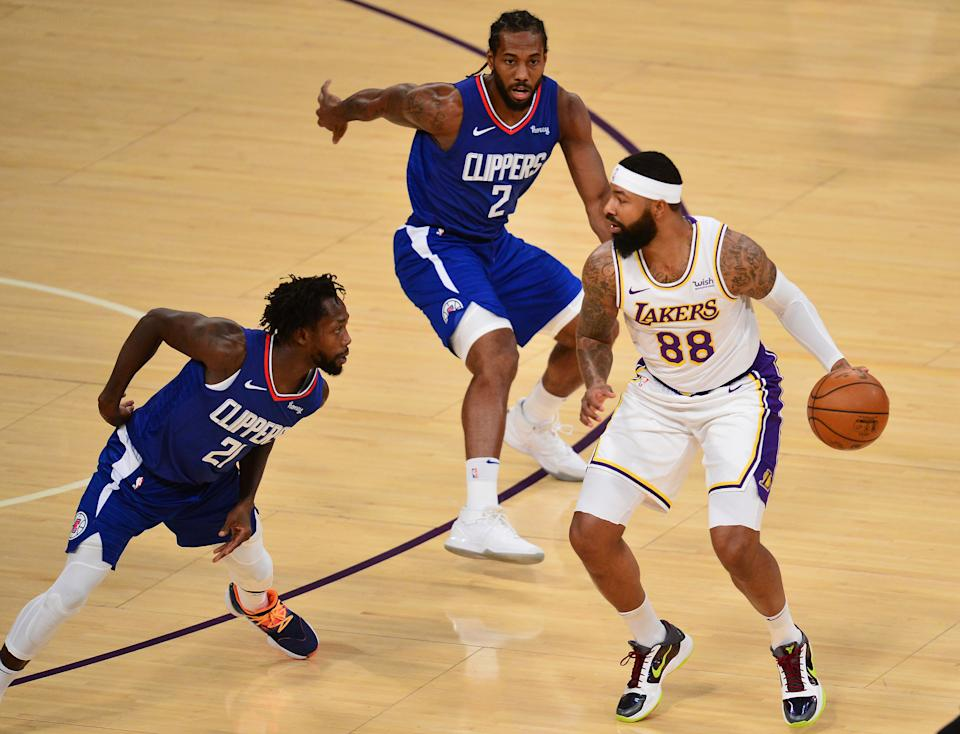 Dec 13, 2020; Los Angeles, California, USA; Los Angeles Lakers forward Markieff Morris (88) moves the ball against Los Angeles Clippers guard Patrick Beverley (21) and forward Kawhi Leonard (2) during the first half at Staples Center.