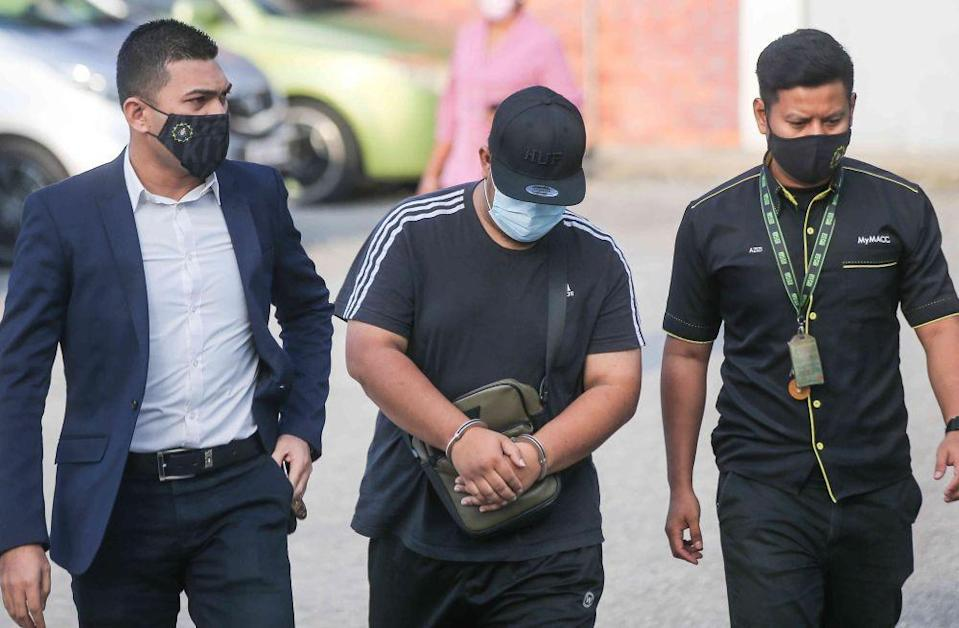 Policeman Mohd Iqbal Fakhruddin Roslan (centre) is pictured at the Ipoh Sessions Court February 24, 2021. — Picture by Farhan Najib