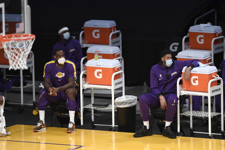 Los Angeles Lakers forward LeBron James, left, and forward Anthony Davis wear masks watch their teammates play during the first half of an NBA preseason basketball game against the Los Angeles Clippers in Los Angeles, Friday, Dec. 11, 2020. (AP Photo/Kyusung Gong)