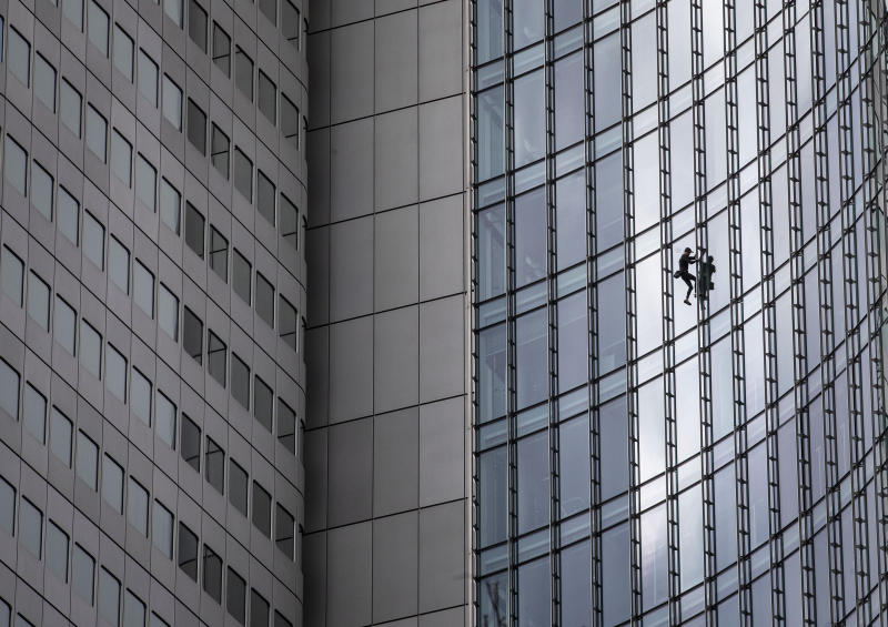"""French urban climber Alain Robert, well known as """"Spiderman"""", climbs down the 'Skyper' highrise in Frankfurt, Germany, Saturday, Sept. 28, 2019. (AP Photo/Michael Probst)"""