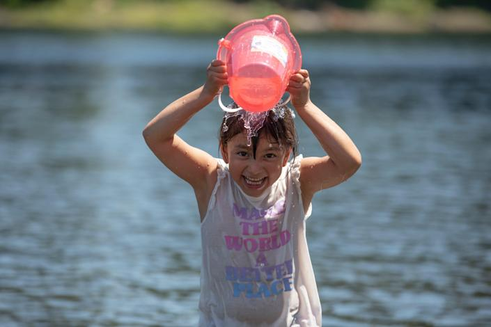 Concepcion Morales, 6, dumps water on her head to cool off from triple-digit temperatures on the Willamette River in Salem, Ore.