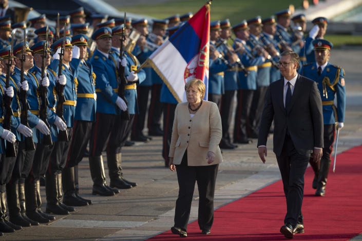 German Chancellor Angela Merkel, center, walks past honor guards while being accompanied by Serbia's president Aleksandar Vucic, front left, in Belgrade, Serbia, Monday, Sept. 13, 2021. Merkel is on a farewell tour of the Western Balkans, as she announced in 2018 that she wouldn't seek a fifth term as Germany's Chancellor. (AP Photo/Marko Drobnjakovic)