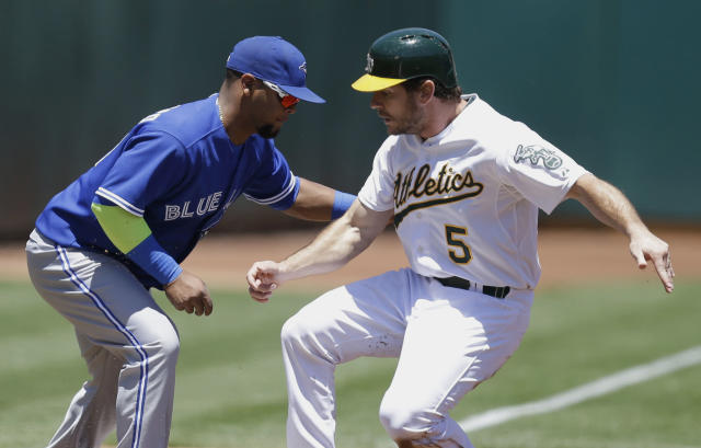 Oakland Athletics' John Jaso, right, beats the tag of Toronto Blue Jays third baseman Juan Francisco as he advances to third base on a sacrifice fly by Alberto Callaspo in the first inning of a baseball game Sunday, July 6, 2014, in Oakland, Calif. (AP Photo/Ben Margot)