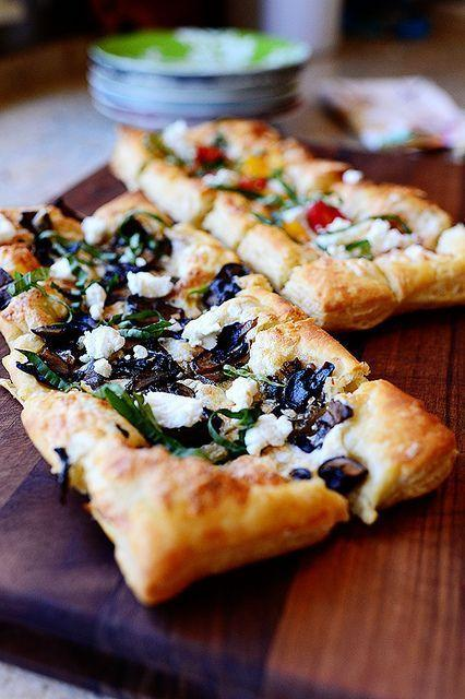 """<p>Flaky puffed pastry is used in place of regular pizza dough for this lighter take on a holiday appetizer. Sprinkle the pizzas with garlicky mushrooms and creamy goat cheese. </p><p><a href=""""https://www.thepioneerwoman.com/food-cooking/recipes/a11436/puffed-pastry-pizza/"""" rel=""""nofollow noopener"""" target=""""_blank"""" data-ylk=""""slk:Get Ree's recipe."""" class=""""link rapid-noclick-resp""""><strong>Get Ree's recipe. </strong></a> </p>"""