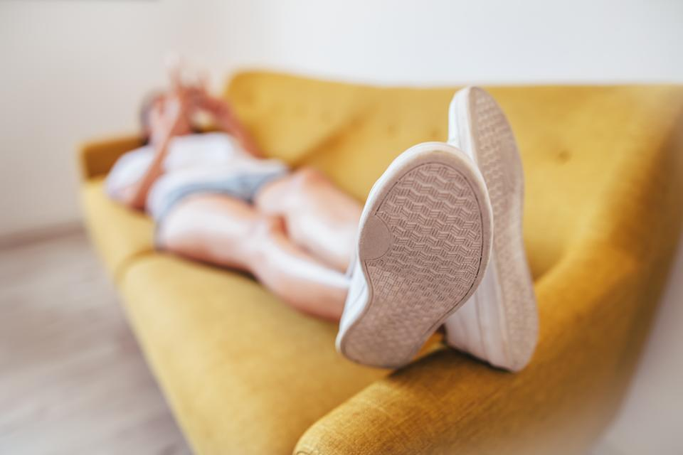 Young woman relaxing sleeping on sofa at home. Focus on foot. Rest concept