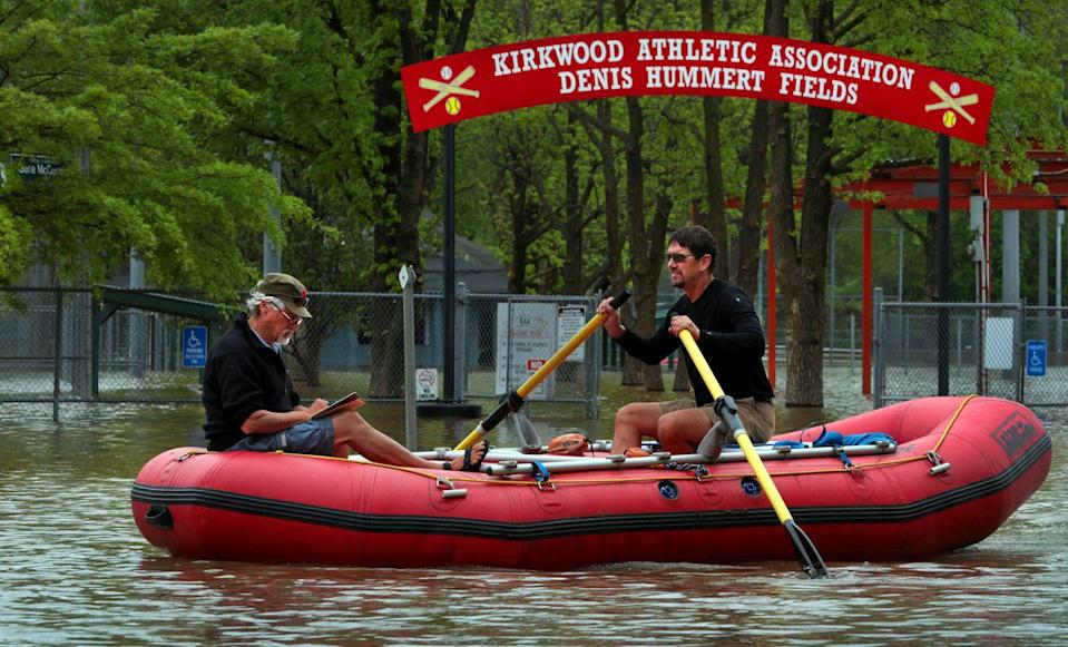 <p>Dan Macheca (right) and Mitch Wieldt paddle through a roadway covered in flood waters from the Meramec River in Missouri on Friday, May 3, 2019.</p>