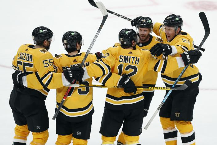 Boston Bruins' Craig Smith (12) celebrates his goal with teammates during the third period of an NHL hockey game against the Buffalo Sabres, Saturday, March 27, 2021, in Boston. (AP Photo/Michael Dwyer)