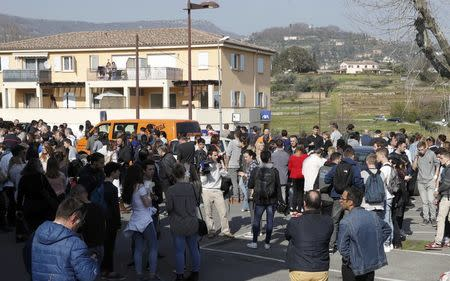 High school students stand near the Tocqueville high school after a shooting incident injuring at least eight people, in Grasse, southern France
