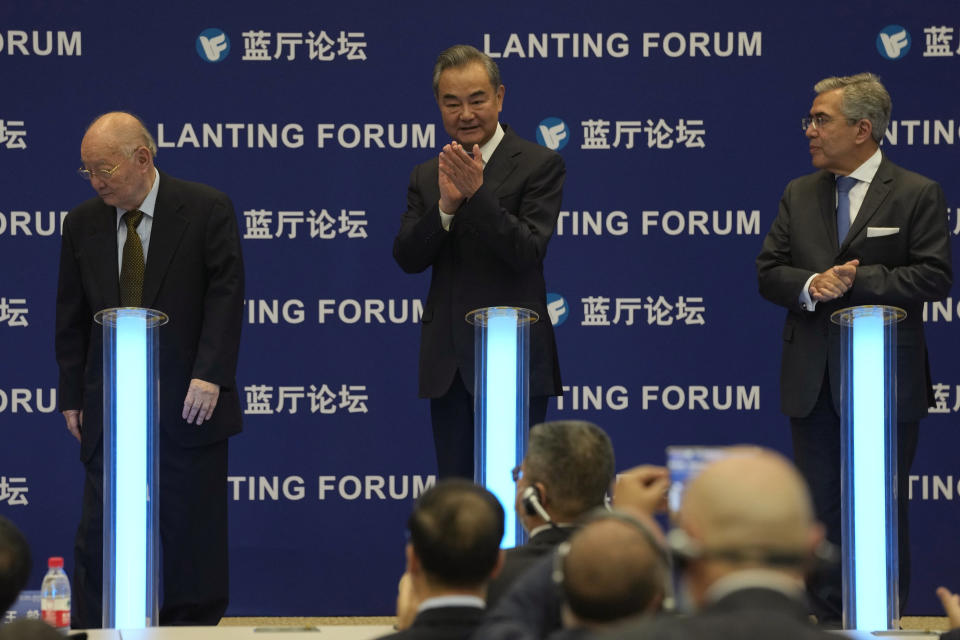 Chinese Foreign Minister Wang Yi, center, applauds during a symposium to mark the 50th anniversary of the People's Republic of China's entry into the U.N. at the Foreign Ministry in Beijing on Friday, June 25, 2021. Foreign Minister Wang Yi said China remains deeply committed to United Nations peacekeeping efforts, where more than 2,400 Chinese troops and police are serving, a contribution that underscores China's increasing prominence in the world body. (AP Photo/Ng Han Guan)