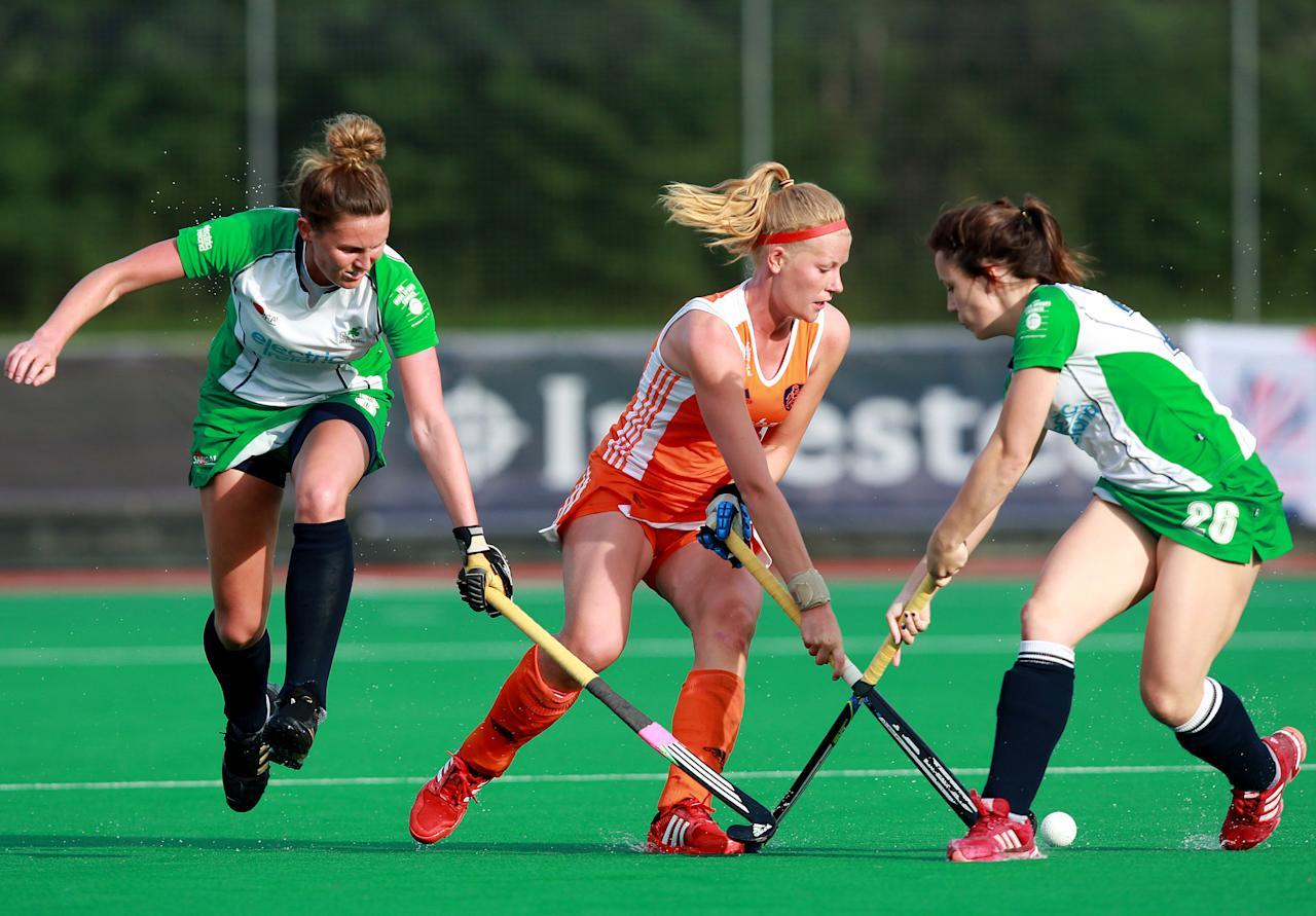 LONDON, ENGLAND - JUNE 7:   Caia van Maasakker of Netherlands battles with Anna O'Flanagan and Nikki Evans of Ireland during the Investec London Cup match between Ireland and Netherlands at The University of Westminster's Quintin Hogg Memorial Sports Grounds on June 7, 2012 in London, England.  (Photo by Jan Kruger/Getty Images)