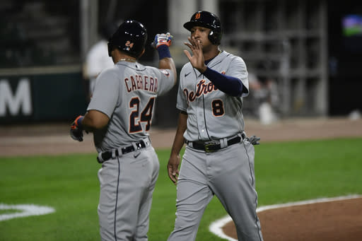 Detroit Tigers' Miguel Cabrera (24) and Jonathan Schoop (8) celebrate after both scored on an Isaac Paredes two-RBI single during the fourth inning of a baseball game against the Chicago White Sox, Monday, Aug. 17, 2020, in Chicago. (AP Photo/Paul Beaty)