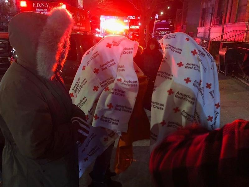 Displaced residents stand outside in freezing temperatures while firefighters fight one of the worst blazes New York City has seen in years.