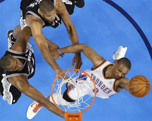 Oklahoma City Thunder guard Russell Westbrook (0) shoots as San Antonio Spurs forward Boris Diaw (33), of France, and center Tim Duncan (21) defend during the first half of Game 4 in the NBA basketball Western Conference finals, Saturday, June 2, 2012, in Oklahoma City. (AP Photo/Sue Ogrocki)