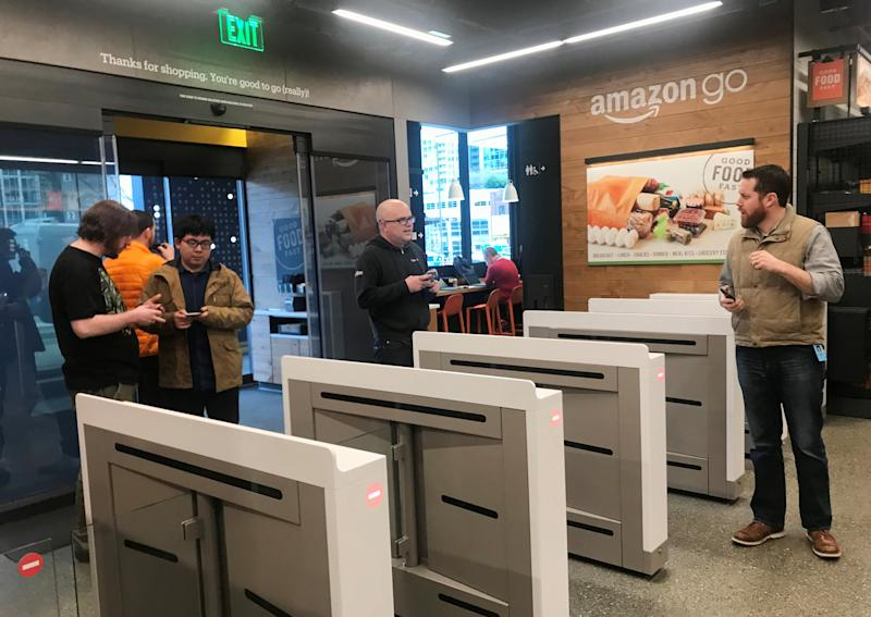 "Shoppers enter the Amazon Go store located in Amazon's ""Day 1"" office building in Seattle"