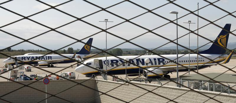 Ryanair planes are seen parked through a fence at Girona airport