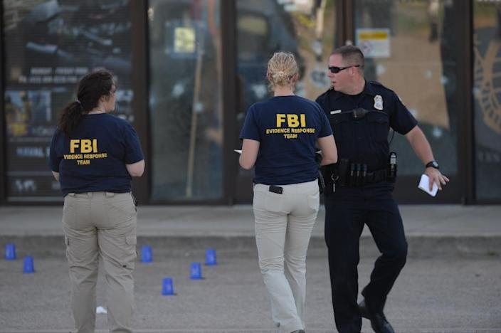 Members of the FBI Evidence Response Team work the scene of a shooting in the parking lot of the Armed Forces Career Center/National Guard recruitment office on July 16, 2015 in Chattanooga, Tennessee (AFP Photo/Jason Davis)
