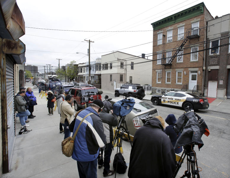 Members of the media stand across from a West New York police department patrol car sit in front of an apartment building Tuesday, April 23, 2013, in West New York, N.J., where Ailina Tsarnaev lives. Tsarnaev, 22, a sister of the Boston Marathon bombing suspects plans to release a statement sometime Tuesday, according to attorney Joseph Ginarte, who said he represents the family. (AP Photo/Mel Evans)