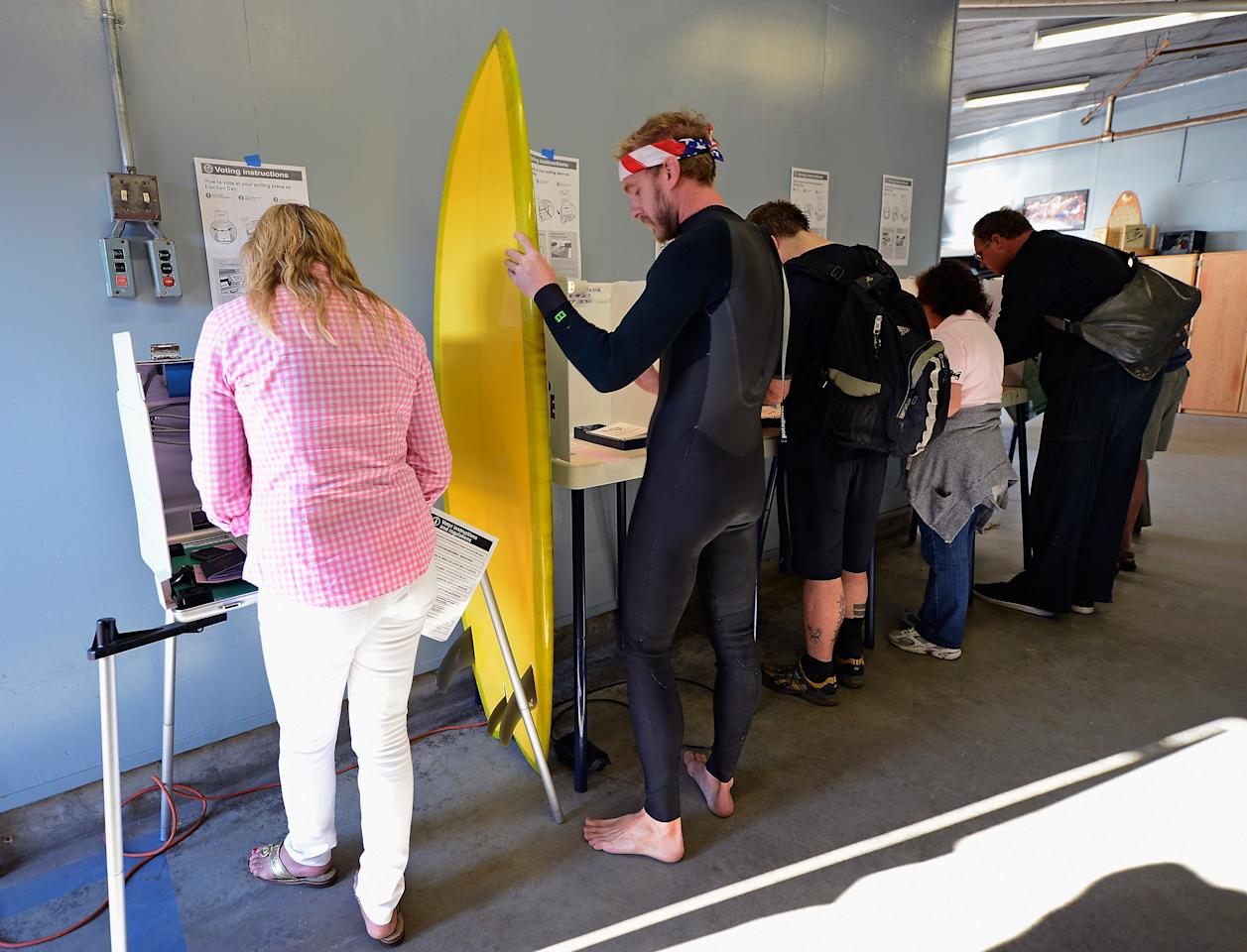 "Mike Wigart (2nd L), 30, secures his surfboard against a ballot box during U.S. presidential elections at a polling station in the garage of the Los Angeles County lifeguard headquarters on November 6, 2012 in Los Angeles, California. Californians will cast ballots in dozens of tight races including Gov. Jerry Brown's tax plan, abolishing the death penalty, easing the state's strict ""three strikes"" sentencing law and also in the Presidential race between Democratic President Barack Obama and Republican candidate Mitt Romney.  (Photo by Kevork Djansezian/Getty Images)"