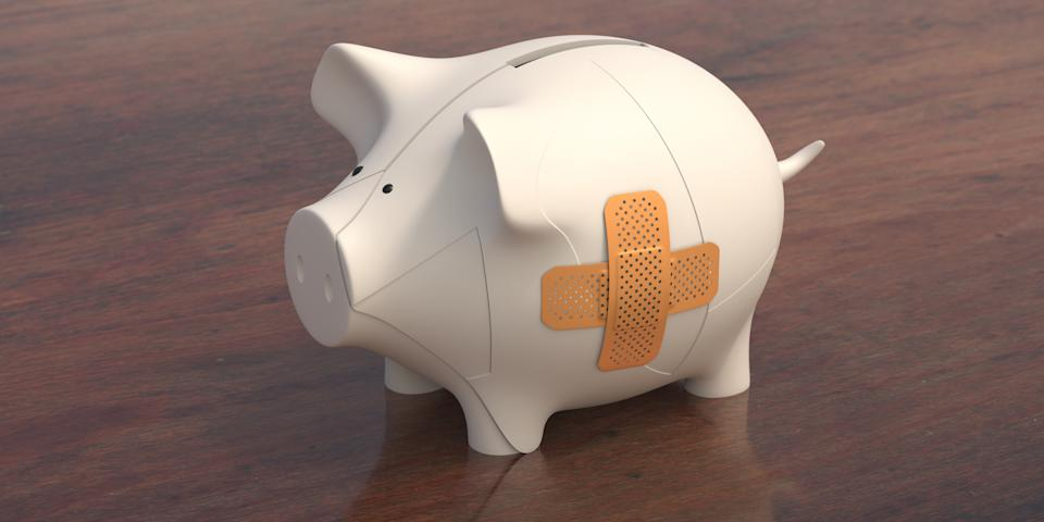 Bank finance aid. Broken piggybank with a patch on wooden desk background. Injured economy care with bandage, cross shape. 3d illustration