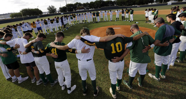 Baseball players from Santa Fe High School and Kingwood Park High School come together around the pitching mound to say a prayer before their game in Deer Park, Texas, Saturday, May 19, 2018. (Photo: David J. Phillip/AP)