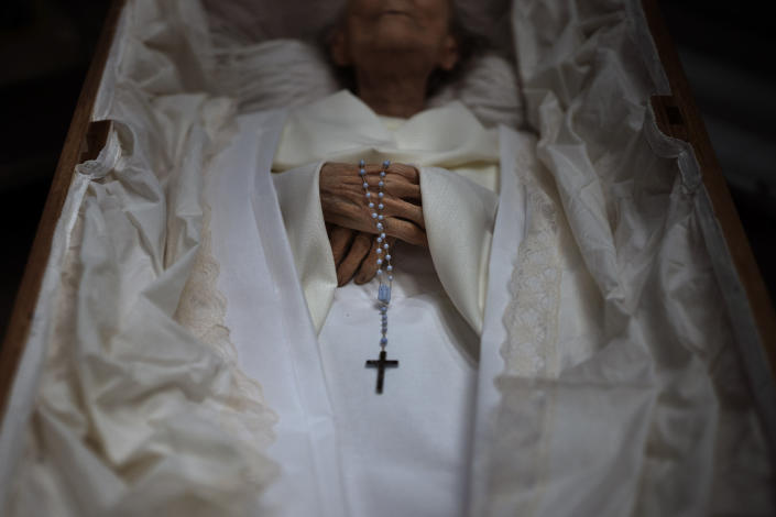 The body of an elderly person is prepared inside a coffin for her funeral at a morgue in Barcelona, Spain, Nov. 5, 2020. The image was part of a series by Associated Press photographer Emilio Morenatti that won the 2021 Pulitzer Prize for feature photography. (AP Photo/Emilio Morenatti)