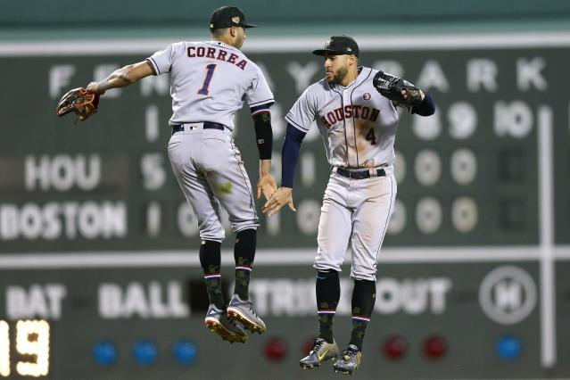 Houston Astros' Carlos Correa (1) and George Springer (4) celebrate after defeating the Boston Red Sox in a baseball game in Boston, Saturday, May 18, 2019. (AP Photo/Michael Dwyer)