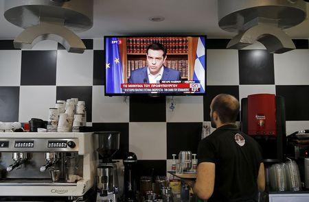 A waiter at a coffee shop follows Greek Prime Minister Alexis Tsipras live television address in Athens, Greece, July 1, 2015. REUTERS/Christian Hartmann