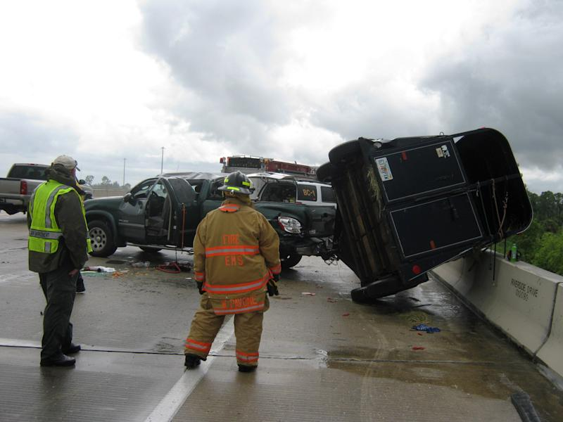 Emergency workers near Punta Gorda, Fla., Monday June 3, 2013 survey a truck with an overturned trailer after an accident on I-75. The trailer was carrying four Llamas. The Llamas are being evaluated at a veteranarian and the driver was hospitalized in stable condition. (AP Photo/DFC Kevin Bordner)