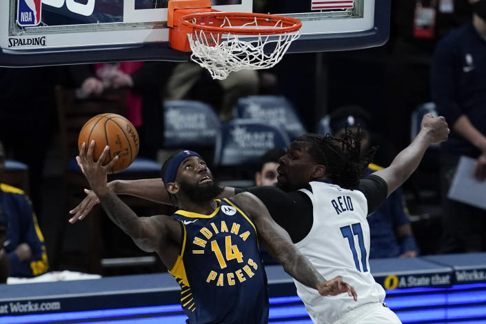 Indiana Pacers' JaKarr Sampson (14) goes up for a dunk against Minnesota Timberwolves' Naz Reid (11) during the first half of an NBA basketball game, Wednesday, April 7, 2021, in Indianapolis. (AP Photo/Darron Cummings)