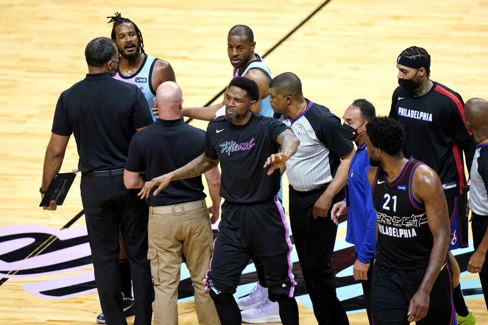 Miami Heat forward Udonis Haslem, center, gestures near Philadelphia 76ers center Joel Embiid (21) afterHeat forward Trevor Ariza, left, was called for a foul during the first half of an NBA basketball game Thursday, May 13, 2021, in Miami. (AP Photo/Lynne Sladky)