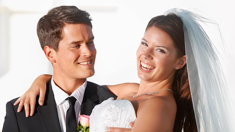 Smiling couple on wedding day resemble bride and groom turning profit off wedding guests at cash bar
