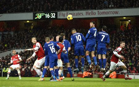 Arsenal's Theo Walcott (L) hits a free kick wide during their English Premier League soccer match against Cardiff City at the Emirates Stadium in London January 1, 2014. REUTERS/Dylan Martinez