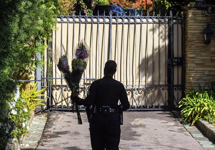 <p>A Los Angeles police officer carries flowers left by a mourner to the front gate of the home of Nancy Reagan in the Bel-Air district of Los Angeles. <i>(Photo: Ringo H.W. Chiu/AP)</i></p>