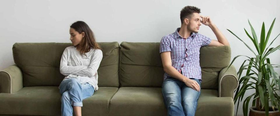 Husband and wife sitting on different sides of couch