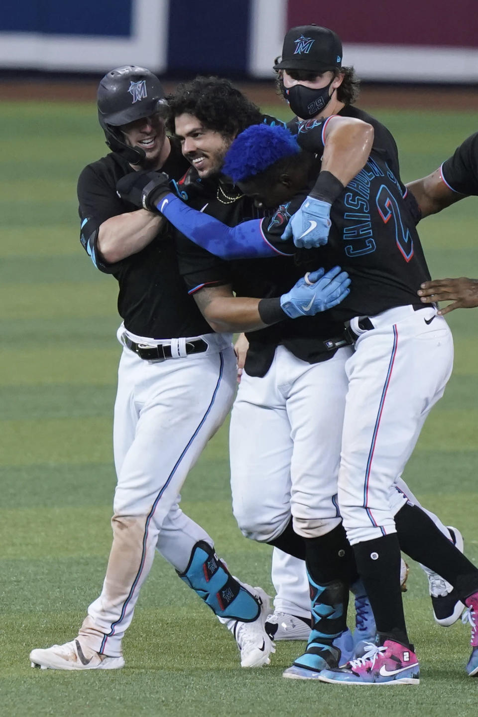 Miami Marlins' Jorge Alfaro, center, is congratulated after he hit a double in the 10th inning to drive in the winning run in the team's baseball game against the San Francisco Giants, Saturday, April 17, 2021, in Miami. The Marlins won 7-6. (AP Photo/Marta Lavandier)