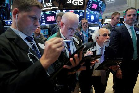 Traders work on the floor at the New York Stock Exchange (NYSE) at the end of the day's trading in Manhattan, New York