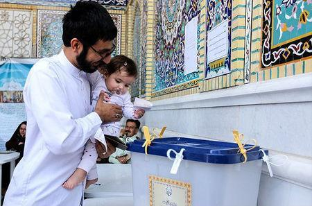 An Iranian man holds a girl as he casts his vote during a second round of parliamentary elections, in Shiraz, Iran April 29, 2016. Farsnews.com/Handout via REUTERS