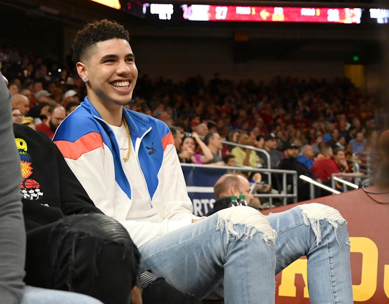 LaMelo Ball sits courtside at a college basketball game.