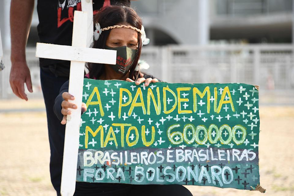 A woman takes part in a protest in front of Planalto Palace in Brasilia on the day Brazil is expected to reach the milestone of 600,000 people killed by the novel coronavirus COVID-19, on October 8, 2021. - The coronavirus has killed at least 4,830,270 people since the outbreak emerged in China in December 2019, with nearly 600,000 of those just in Brazil, according to an AFP compilation of official data. (Photo by EVARISTO SA / AFP) (Photo by EVARISTO SA/AFP via Getty Images)