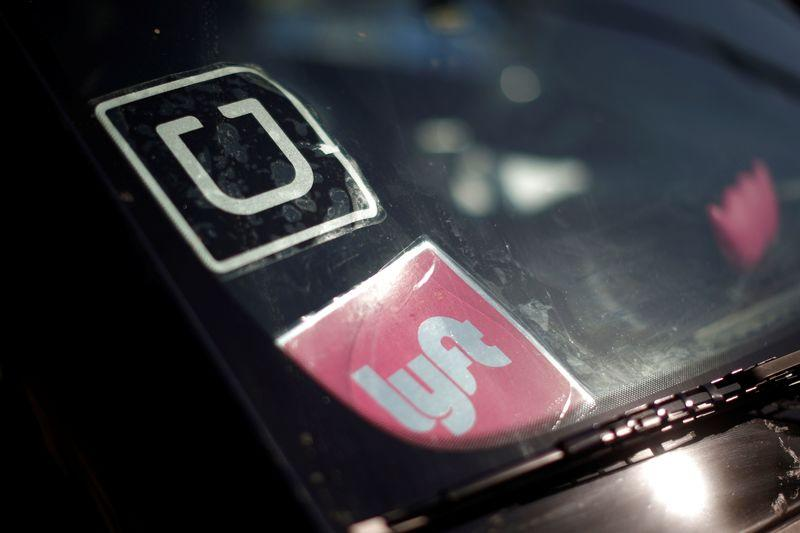 File photo of a driver displaying Uber and Lyft ride sharing signs on his car windscreen in Santa Monica