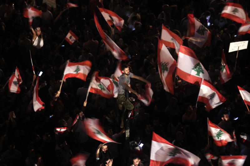 """FILE - In this Oct. 21, 2019 file photo, anti-government protesters wave Lebanese flags and chant,  """"the people want to bring down the regime"""" outside the office of legislator Mohammed Raad, the powerful head of Hezbollah's parliamentary bloc, in Beirut, Lebanon. Lebanon's protests have shown unusual overt anger at the country's powerhouse, Hezbollah. (AP Photo/Hassan Ammar, File)"""