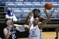 North Carolina forward Day'Ron Sharpe and forward Armando Bacot (5) reach for a rebound next to Duke forward Matthew Hurt (21) during the first half of an NCAA college basketball game in Chapel Hill, N.C., Saturday, March 6, 2021. (AP Photo/Gerry Broome)