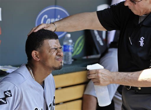 Chicago White Sox' Eduardo Escobar closes his eyes as trainer Herm Schneider sprays him with cool water for relief from oppressive heat and high humidity during a baseball game against the Minnesota Twins Wednesday, June 27, 2012 in Minneapolis. (AP Photo/Jim Mone)