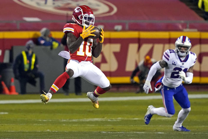 Kansas City Chiefs wide receiver Tyreek Hill (10) catches a pass ahead of Buffalo Bills safety Jordan Poyer, right, during the first half of the AFC championship NFL football game, Sunday, Jan. 24, 2021, in Kansas City, Mo. (AP Photo/Jeff Roberson)