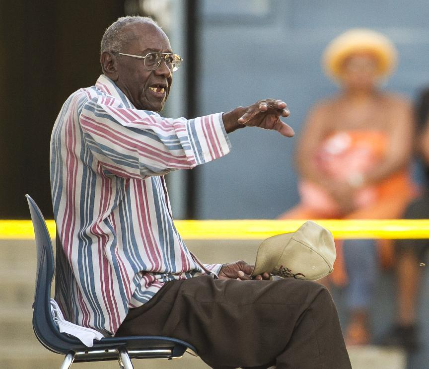 Senior driver Preston Carter, 100, talks with police officers after police say his car went onto a sidewalk and plowed into a group of parents and children outside a South Los Angeles elementary school, Wednesday, Aug. 29, 2012, in Los Angeles. Nine children and two adults were injured in the wreck. (AP Photo/Damian Dovarganes)