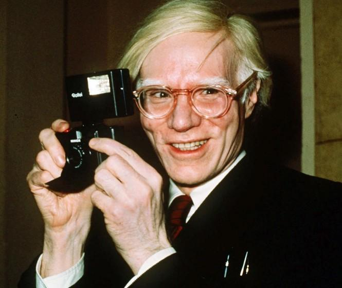 FILE - In this 1976 file photo, pop artist Andy Warhol smiles in New York. A federal appeals court sided with a photographer Friday, March 26, 2021, in her copyright dispute over how a foundation has marketed a series of Andy Warhol works of art based on her pictures of Prince. (AP Photo/Richard Drew, File)