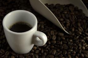 Double espresso cup of coffee against blended coffee beans and measure scoop background.