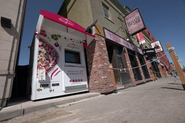 A slice of life during the pandemic: Senate Tavern's automated pizza vending machine in the ByWard Market, just outside the shuttered sports bar. This machine and another one in Old Ottawa South each dispense as many as 60 hot pizzas a day. (Francis Ferland/CBC - image credit)