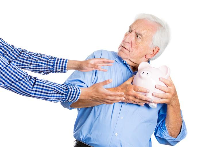Older man holding piggy bank out of reach of grasping arms.